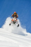 Athlete on a snowmobile moving  in the mountains Royalty Free Stock Image
