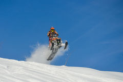 Athlete on a snowmobile moving  in the mountains Stock Photography