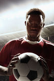 Athlete with soccer ball in stadium stock image