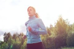 Athlete sportsmen girl running in morning sunrise Stock Photography
