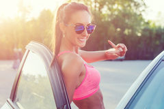 Athlete sporty fit young woman in sports bra wearing sunglasses standing leaning on car with door open looking at camera Royalty Free Stock Photo