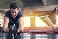 Athlete sporty man doing exercise with abs roller wheel to strengthen his abdominal muscle in gym.  stock photos