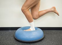 Athlete with a sprained ankle doing strengthening and balance exercises on a bosu ball royalty free stock photography