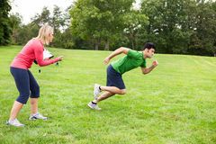 Athlete sprinting. A fitness coach timing an athlete sprinting in a field Stock Images