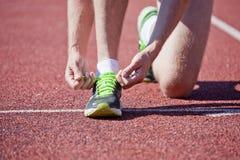 Athlete on the stadium track tying shoelaces Stock Image
