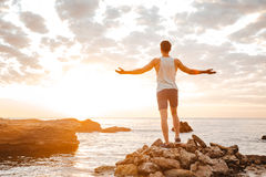 Athlete standing backwards with arms raised at the rocky beach Stock Image
