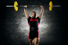 The athlete is standing with a barbell above his head. stock photos