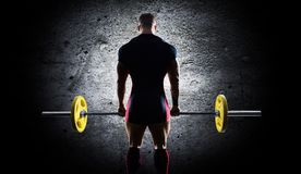 The athlete is standing with a barbell in his hands. Back view Stock Images