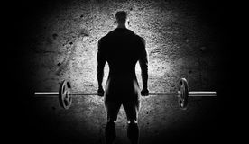 The athlete is standing with a barbell in his hands. Back view Royalty Free Stock Photo