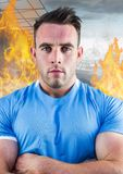 Athlete standing with his arms crossed against fire in background. Digital composition of athlete standing with his arms crossed against fire in background Stock Photos