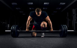 Athlete is standing on his knee and near the bar and is preparin. Athlete is standing on his knee and near the bar in the gym and is preparing to make a deadlift Stock Images