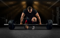 Athlete is standing on his knee and near the bar and is preparing to make a deadlift stock photo