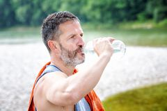 Athlete standing outdoors and drinking from bottle. Portrait of handsome athlete standing outdoors and drinking from bottle Stock Photography