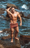 Athlete stands on a rock by the sea Stock Image