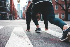 Athlete in start pose on city street. Man runner preparing to running through big urban streets stock images