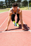 Athlete on a starting block about to run. Determined athlete on a starting block about to run Royalty Free Stock Photography