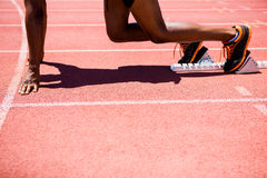 Athlete on a starting block about to run. Determined athlete on a starting block about to run Royalty Free Stock Photos