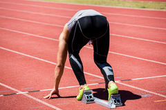 Athlete on a starting block about to run. Rear view of determined athlete on a starting block about to run Royalty Free Stock Photo