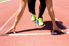 Athlete on a starting block about to run. On running track Royalty Free Stock Photos