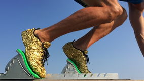 Athlete in Starting Blocks Slow Motion. Athlete in gold running shoes takes off from starting blocks on a race track in slow motion against blue sky stock video