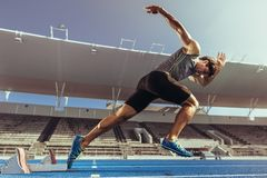 Sprinter taking off from starting block on running track. Athlete starting his sprint on an all-weather running track. Runner using starting block to start his royalty free stock image