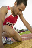 Athlete At Starting Line. Young male athlete in starting block at racetrack Stock Photography
