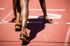 Athlete on a starting line about to run. On running track Royalty Free Stock Photography