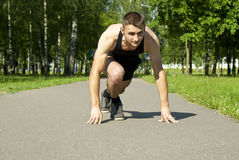 Athlete starts on the path in the park Stock Photography