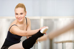 Athlete stretches herself near barre Stock Images