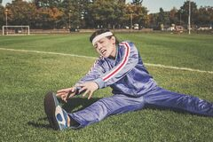 Athlete stretching on field Royalty Free Stock Photos