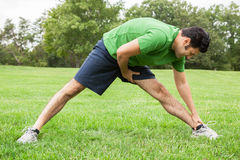 Athlete stretching legs. Handsome 30s athlete stretching legs in a field Stock Photo