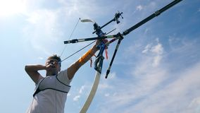 Athlete strings a bow while practicing on a shooting range. 4K stock video footage