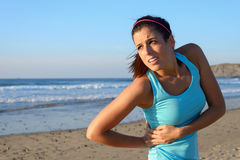 Athlete suffering side kidney pain. Fitness woman with side kidney pain. Female athlete with painful injury or spasm in serratus muscles Stock Photography
