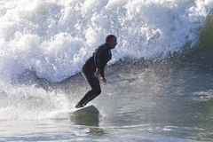 Athlete surfing on Santa Cruz beach in California Stock Images