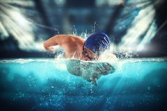 Athlete swims in a blue deep pool. Young athlete trains swimming in the pool Royalty Free Stock Photography