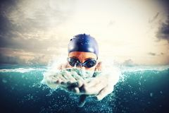 Athlete swims in a blue deep water. Young athlete trains swimming in the sea Stock Photo