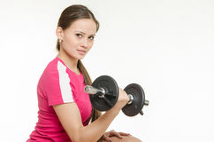 Athlete swings dumbbells muscles of the right hand Royalty Free Stock Photos