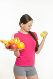 Athlete swings his left hand holding a plate of fruit in his right hand Royalty Free Stock Photos