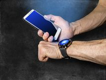 Athlete syncs your smartphone and smart watch on on your hand stock photography