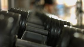 Athlete takes a dumbbell for training. Dumbbells in gym. Many exercise weights - iron dumbbells in gym stock video