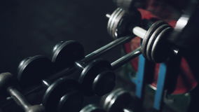 Athlete takes a dumbbell for training. Dumbbells in gym. stock video