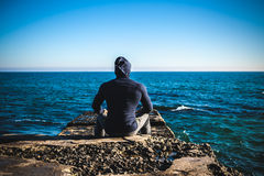 Athlete taking break sitting on rocks with sea horizon. On a beach Royalty Free Stock Photo