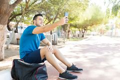 Athlete Taking Selfie Using Mobile Phone While Sitting In Park. Handsome young athlete taking selfie using mobile phone while sitting in park Stock Photo
