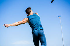 Athlete throwing discus in stadium. Rear view of athlete throwing discus in stadium during competition royalty free stock photos
