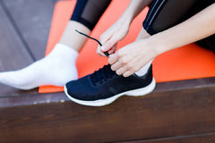 Athlete ties shoelaces on sneaker. In gym, sitting on rug on the wooden floor Stock Image