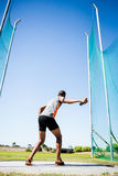 Athlete about to throw a discus. Rear view of athlete about to throw a discus in stadium stock photography