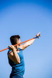Athlete about to throw a javelin. Determined athlete about to throw a javelin in the stadium Royalty Free Stock Image