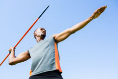 Athlete about to throw a javelin. Low angle view of determined athlete about to throw a javelin in the stadium stock photos