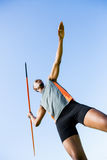 Athlete about to throw a javelin. Low angle view of determined athlete about to throw a javelin in the stadium Stock Image