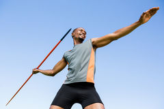 Athlete about to throw a javelin. Low angle view of happy athlete about to throw a javelin in the stadium Royalty Free Stock Image